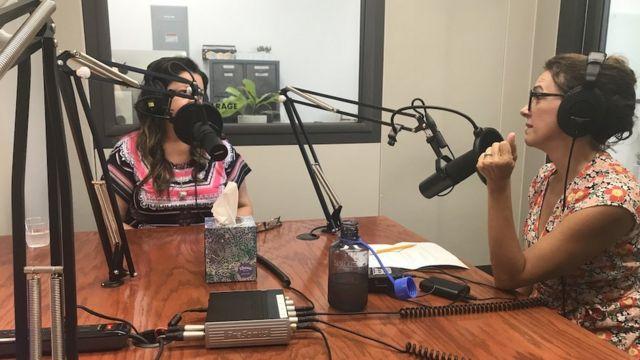 Heloiza Barbosa e Paula Costa usando fones de ouvido e microfones