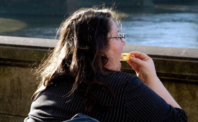 Kızarmış patates yiyen kilolu bir kadın