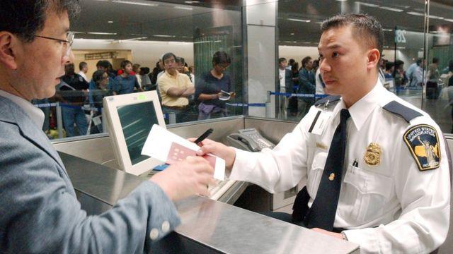 Un oficial de migración entrevista a un inmigrante.