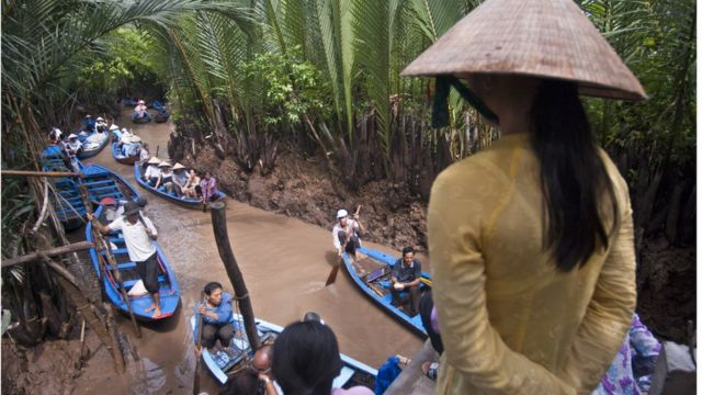 Woman and rowing boats on Mekong river