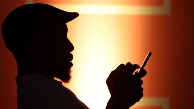 telefonundan internete giren bir adam silüeti