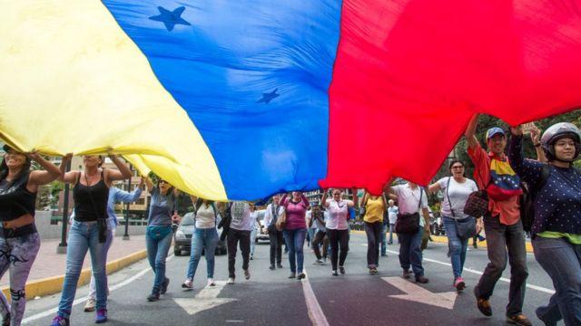 Manifestantes con una gran bandera venezolana.