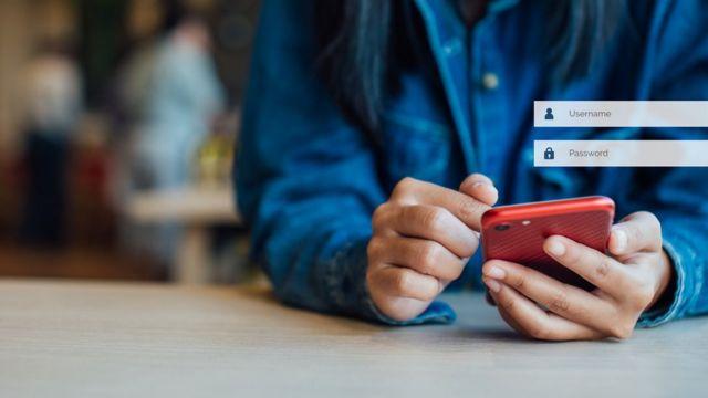 Persona con teléfono poniendo nombre de usuario y contraseña.
