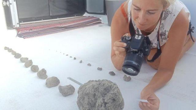 Larissa Brill toma fotos de las piedras pómez recogidas en el Pacífico.