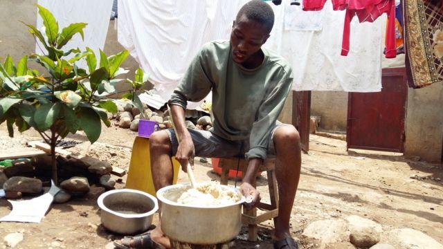 Un étudiant prépare une pâte de manioc, que ses camarades et lui vont manger avec des haricots.