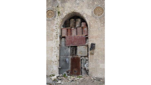 Barriles y cajas apiladas en un arco para evitar los daños de los bombardeos