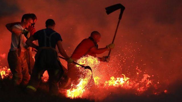 Bomberos combaten un incendio descontrolado con batidores en Winter Hill, cerca de Bolton, Reino Unido, el 28 de junio de 2018