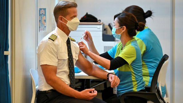 香港某社区疫苗接种中心内一位国泰航空公司外籍机长(左)接受一位女工作人员(右)注射科兴新冠病毒疫苗(23/2/2021)