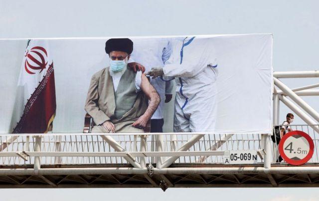 پوستر رهبر ایران در حال زدن واکسن در اقدامی که تشویق برای واکسن کووایران برکت توصیف شده است