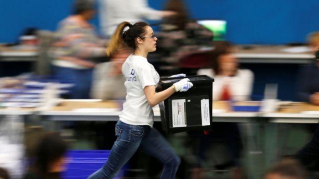 امرأة تجري وهي تحمل صندوق انتخابي