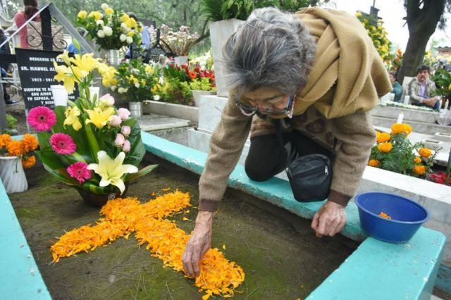 Mujer coloca flor de cempasúchil en una tumba.