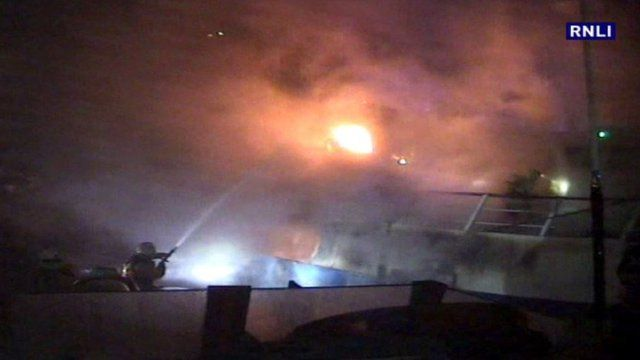 Firefighters tackle a blaze on a fishing boat
