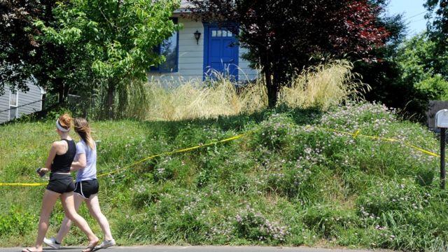 Dos personas caminan frente a la entrada de la casa de Kaplan.