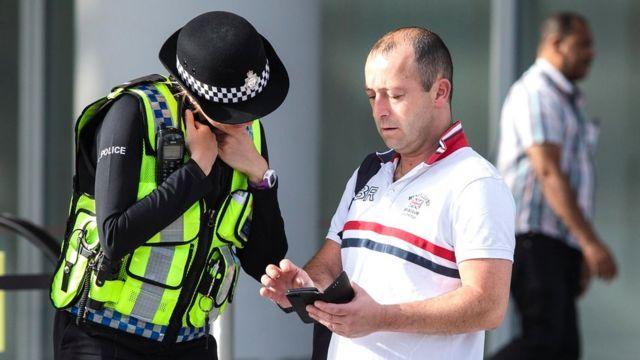 Сотрудница полиции разговаривает с прохожим