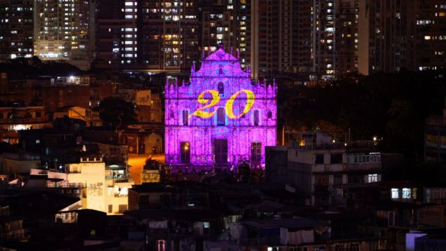 The number 20 is projected onto the ruins of St Paul