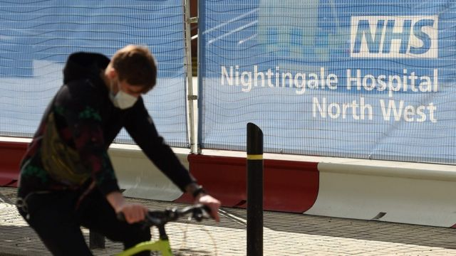 A man wearing a face masks cycles past the NHS Nightingale Hospital North West in Manchester City Centre