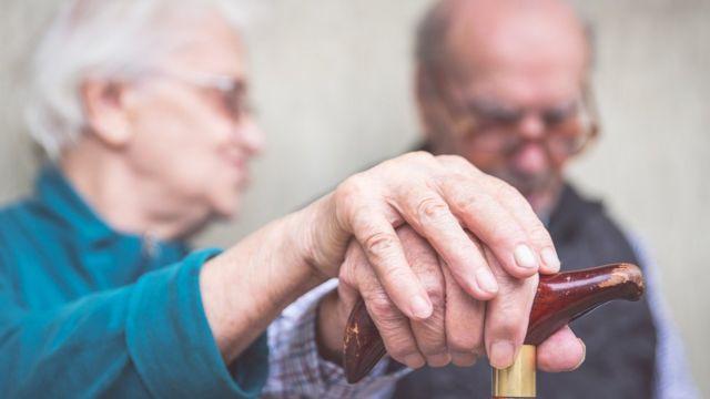 Dos ancianos sentados, él con bastón y ella cogiéndole una mano.