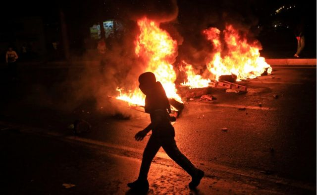 """A masked protester runs past garbage bins set on fire by supporters of the pro-Kurdish Peoples""""s Democratic Party (HDP) in Diyarbakir, in Turkey""""s predominantly Kurdish southeast, Sunday, Nov. 1, 2015."""