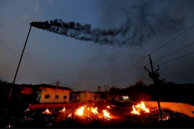 Parentes realizando funerais de vítimas de Covid na cidade de Bhopal, no centro da Índia