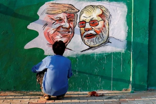 A man dey paint U.S. President Donald Trump and India Prime Minister Narendra Modi ontop wall