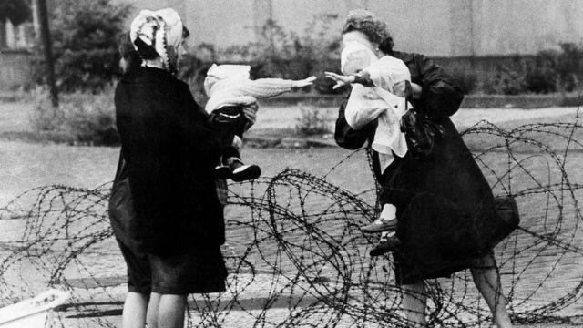 Madres separadas por los alambres que configuraron el primer muro de Berlín en agosto de 1961.