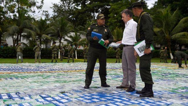 El presidente de Colombia, Juan Manuel Santos, parado sobre el cargamento de 12 toneladas de cocaína incautadas al Clan del Golfo.