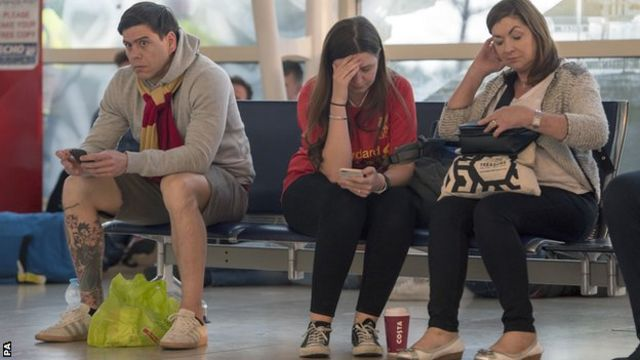 Liverpool fans look miserable in the airport