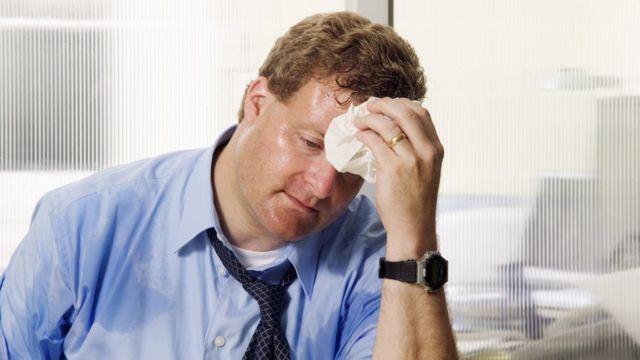 Hombre de negocios sudando en una oficina.