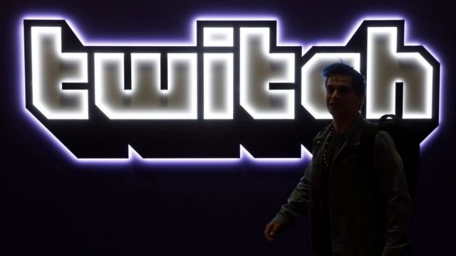 Twitch logo with lights on a wall.