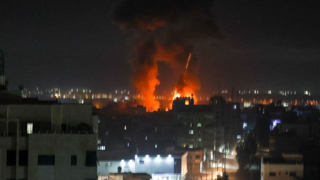 Explosions light-up the night sky above buildings in Gaza City as Israeli forces shell the Palestinian enclave
