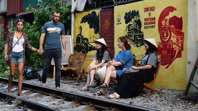 Khách du lịch đến thăm quan đường tàu chạy qua khu phố cổ ở Hà Nội