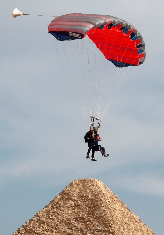 "A professional skydiver carries a tourist as they fly over pyramid Khufu or ""Cheops""."