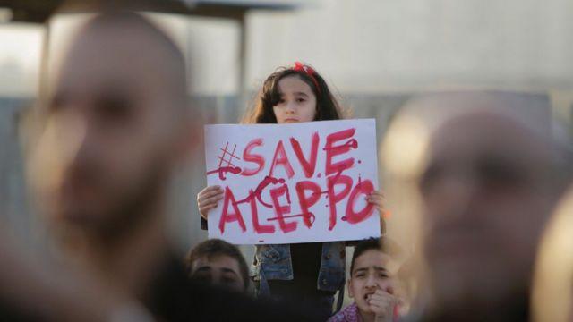 "Umwana w'umukobwa afite icyapa cyanditseho ngo ""Tabara Aleppo"" mu myigaragambyo yabereye i Tripoli na Libani (01/05/2015)"