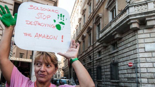 Mulher segura cartaz de protesto em inglês, onde se lê: Bolsonaro, pare de destruir a Amazônia