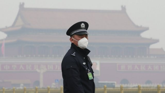 A security officer wearing a mask stands at the Tiananmen Square in haze