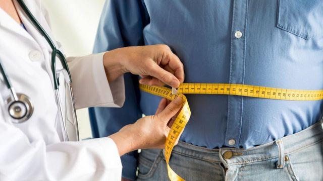 Doctora con un metro midiendo a un paciente