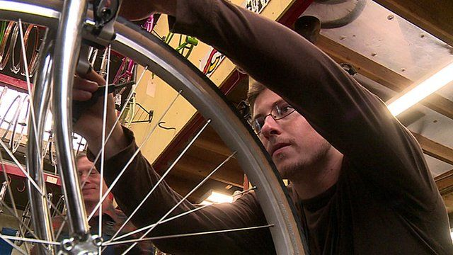Mike, who was helped by a social start-up, fixes a bicycle