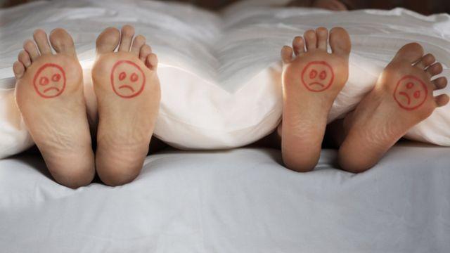 Imagen de unos pies con dibujos de caritas infelices.
