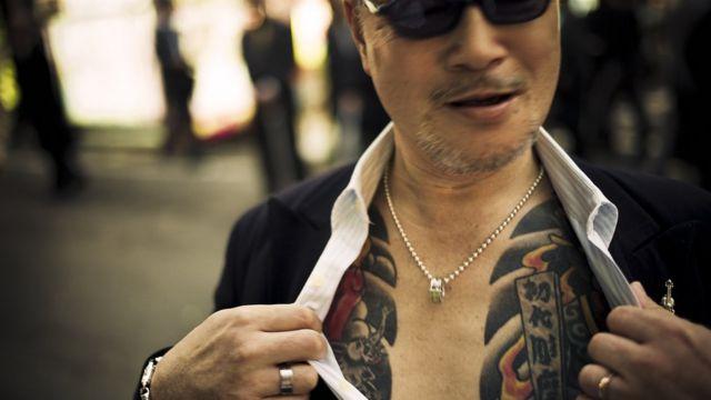 Un hombre mostrando sus tatuajes