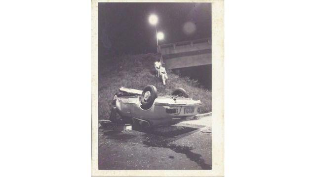 Foto em preto e branco mostra carro de cabeça para baixo em ribanceira