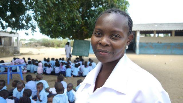 Professora Açucena Mabunda à frente, e sua sala de aula ao fundo; no último plano, outra professora da aula em outra sala-árvore