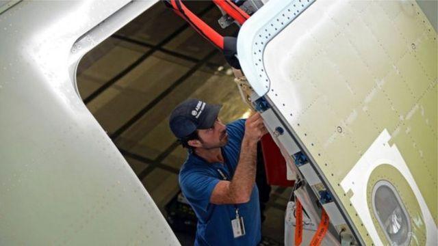 Homem ajustando porta de avião