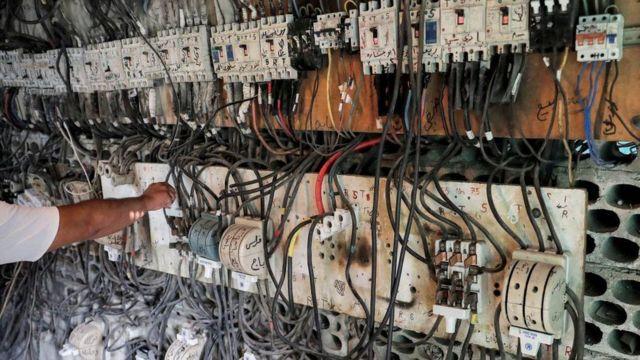 فني يتحكم في لوحة مفاتيح كهربائية تربط المنازل بمولدات كهربائية في إحدى ضواحي العاصمة اللبنانية بيروت