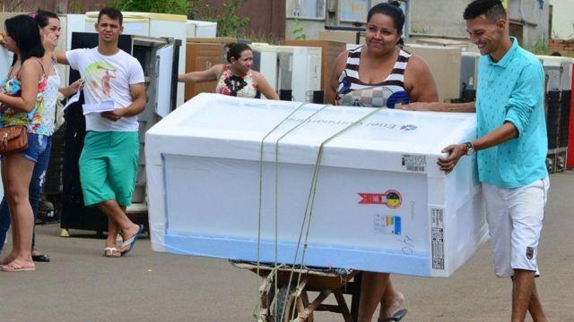 Mulher leva geladeira nova em carrinho de mão durante ação de distribuição