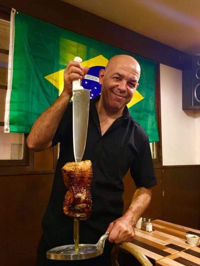 Sandro Pereira, brasileiro que vive na província de Hokkaido, onde foi registrado um forte terremoto no Japão, posa para foto segurando carne e uma faca, com uma bandeira do Brasil ao fundo. Ele trabalha em uma churrascaria na província