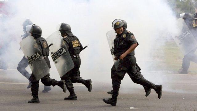 Policías corren durante una protesta en México.