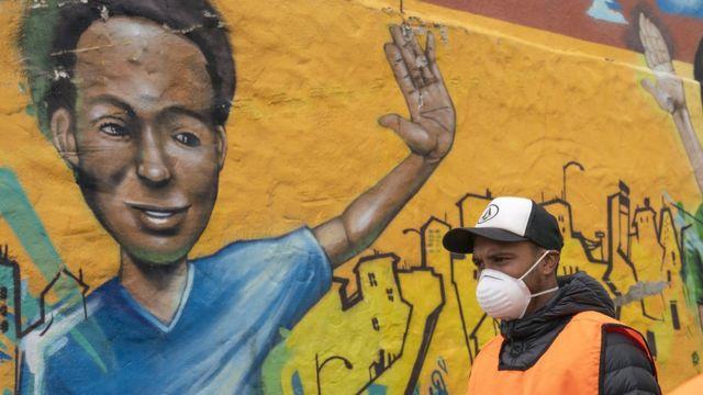 Homem usando máscara na rua na África do Sul diante de mural