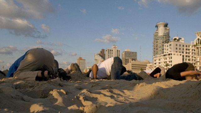 صورة تعبيرية لبعض الناس وهم يحاولون دفن رؤوسهم في الرمال