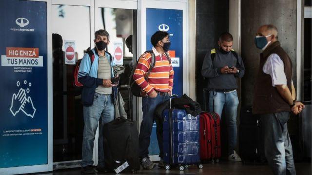 Três passageiros e um segurança do lado de fora de aeroporto