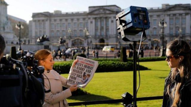 Mulher com jornal sobre discurso de membros da família real